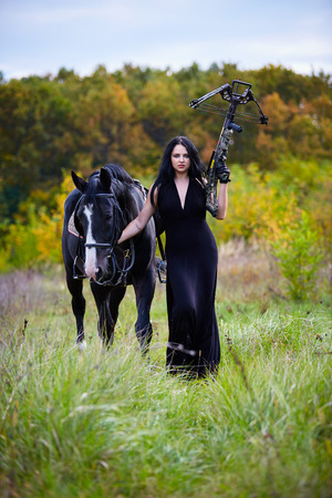 crossbow: Beautiful woman with black horse and crossbow walking in the forest, fantasy concept
