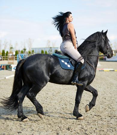 jinete: Mujer joven hermosa que monta un caballo en un hipódromo Foto de archivo