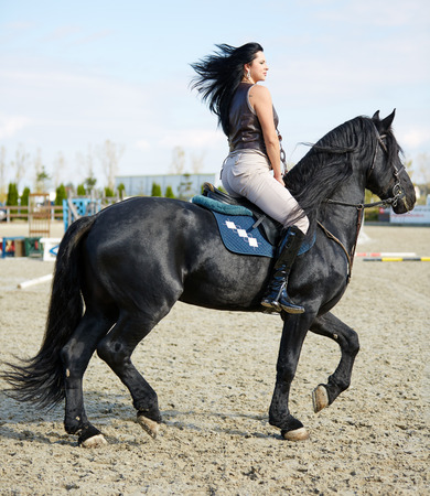 Schöne junge Frau auf einem Pferd auf einer Pferderennbahn Standard-Bild