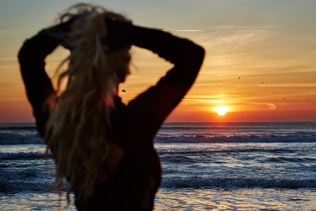 cabello rubio: Gorgeous woman on the sea shore at sunrise, back view