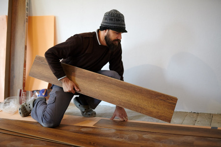 Handy man worker laying parquet in a room