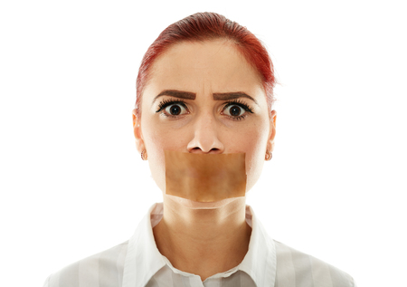 covering mouth: Muted businesswoman with adhesive tape over her mouth, closeup Stock Photo