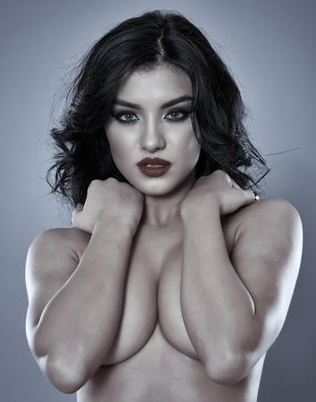 seins nus: Superbe topless dame hispanique, close-up glamour sur fond gris Banque d'images