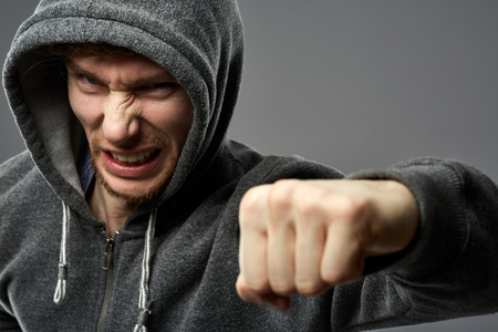 scheming: Closeup portrait of threatening gangster wearing a hood, representing the concept of danger
