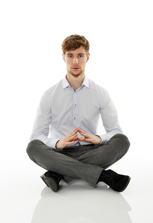 legs crossed: Calm and relaxed businessman meditating, sitting with his legs crossed