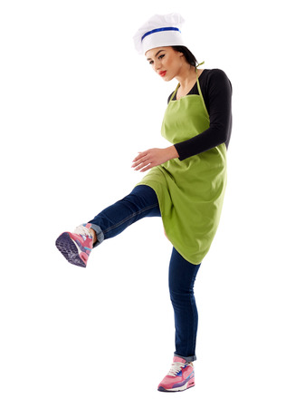invisible object: Studio shot of a latino woman cook kicking an invisible object with her leg Stock Photo