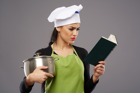 kitchen aprons: Beautiful woman cook holding a stainless steel pot and reading a recipe