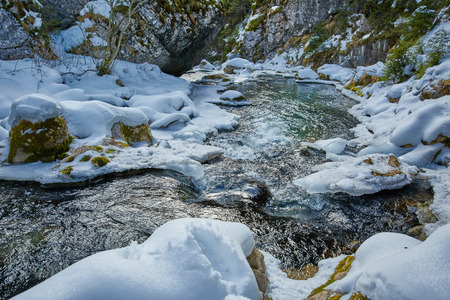 icy: Closeup of a frozen mountain river flowing through icy rocks