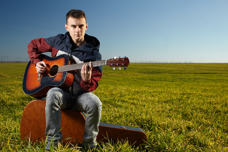 boy playing guitar: Teenage boy playing guitar outdoor in a grass field