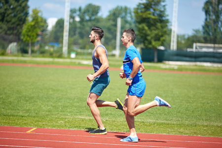 Two athletes friends running on a stadium track photo