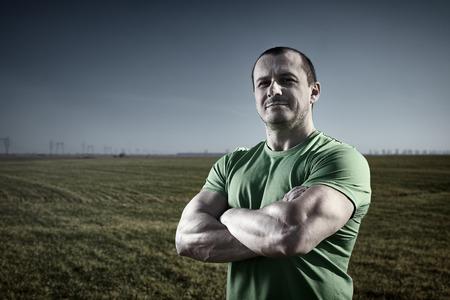 hombre fuerte: Hombre agricultor fuerte en camiseta que presenta cerca de un campo de centeno al atardecer