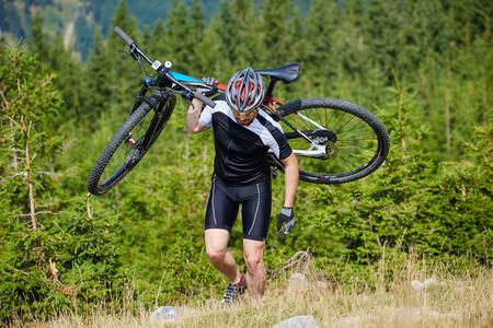 andando en bicicleta: Ciclista que lleva su bicicleta de montaña en una empinada cuesta arriba