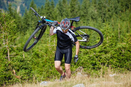 mountain bicycling: Cyclist carrying his mountain bike on a steep uphill