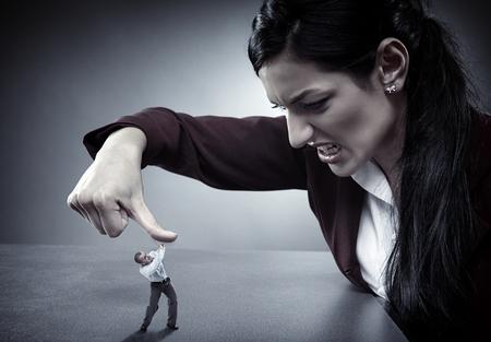 personne en colere: Lady patron écraser un employé en vertu de son pouce comme un bug Banque d'images