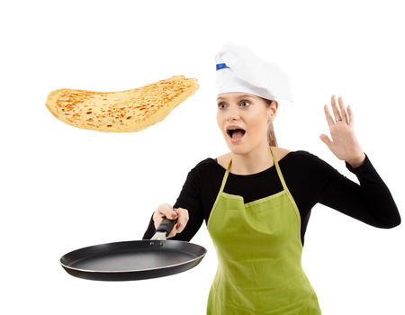 woman cooking: Beginner cook flipping pancakes, trying not to drop them