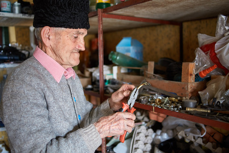 deprecated: Senior man in his tool shed trying to fix something