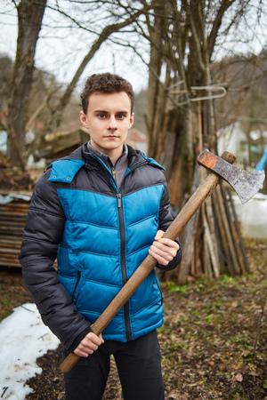 axes: Handsome teenage country boy holding axes outdoor