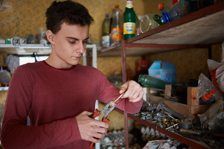 deprecated: Teenage boy with pliers and various tools doing some diy project