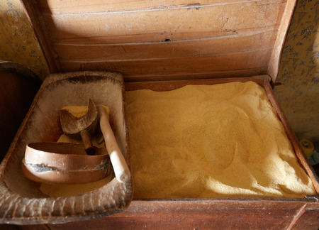 Crate with corn flour and wooden kitchen utensils