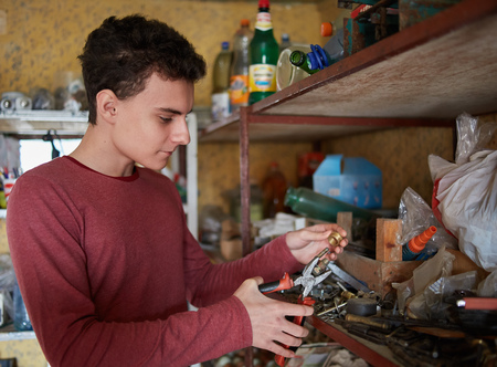 Teenage boy with pliers and various tools doing some diy project