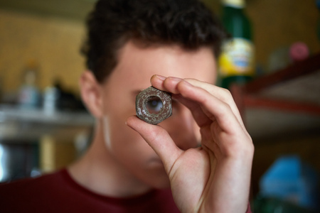 deprecated: Teenage boy holding a rusty screw nut and looking through it