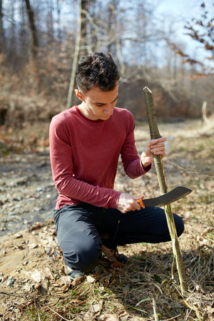 resourceful: Teenage boy in the forest making a tool using a machete Stock Photo