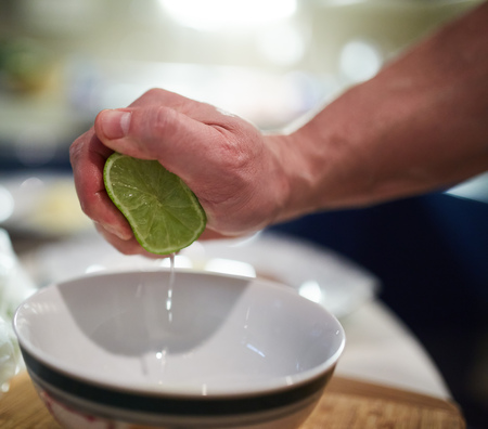 squeezing: Hands of male chef squeezing limes in a bowl