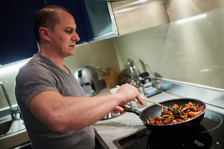 Man cooking at home alone a thai recipe in wok pans