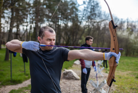 hombre disparando: Hombre disparando con su arco en un alcance en exteriores