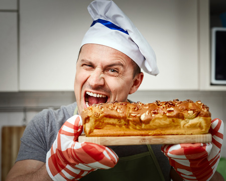 man nuts: Happy cook holding a board with a cake with walnuts freshly out of the oven