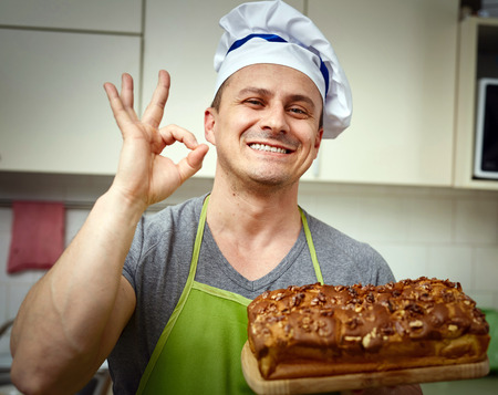 cook out: Happy cook holding a board with a cake with walnuts freshly out of the oven