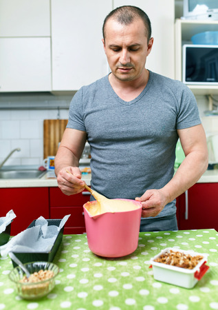 man nuts: Man cooking alone at home a cake recipe Stock Photo