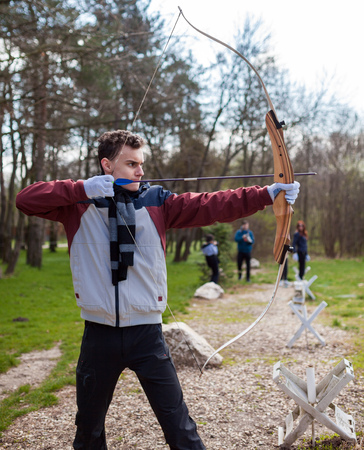 bowman: Boy archer shooting with his bow at an outdoor archery range Stock Photo