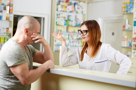 Upset customer at the counter of a pharmacy Stock Photo