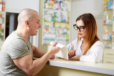 recetas medicas: cliente enojado en una farmacia que muestra el recibo para el farmacéutico