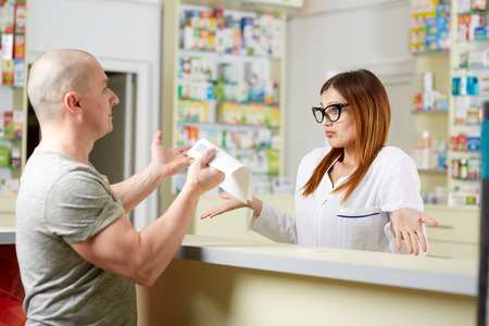 Angry client at a pharmacy showing the receipt to the pharmacist Standard-Bild