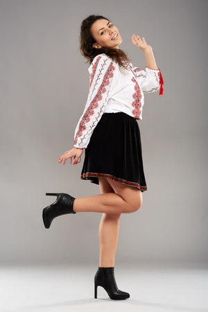 ethnology: Young Romanian woman in traditional folklore costume on gray background