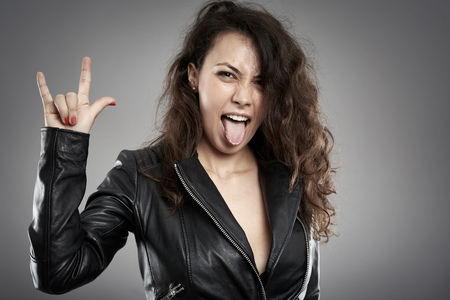 black out: Rock chick in leather jacket yelling with her tongue out Stock Photo