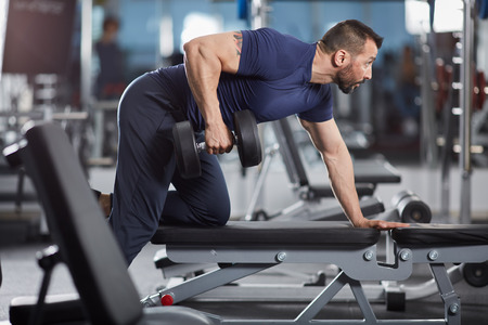 lats: Man doing dumbbell row for back workout in the gym