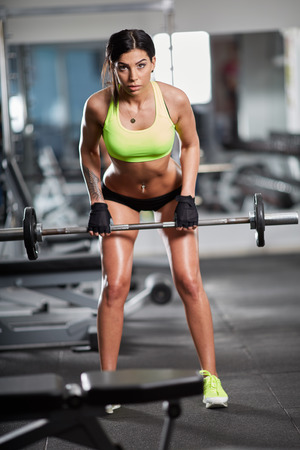 lats: Young woman doing barbell rows for back workout in the gym
