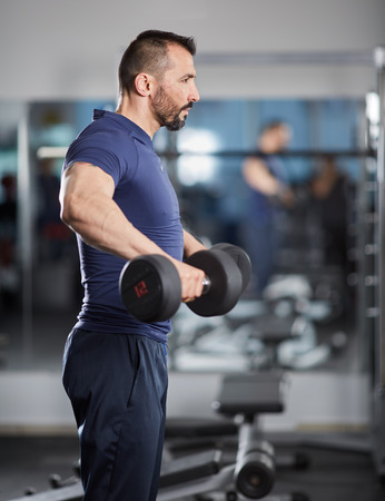muscle guy: Man doing shoulder workout with dumbbells in the gym Stock Photo