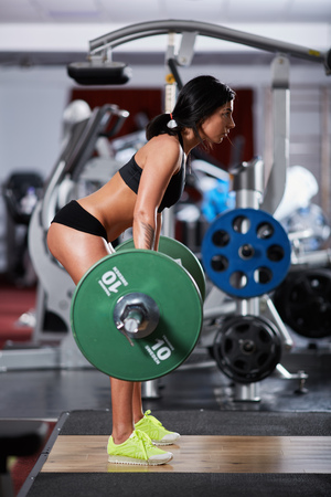 dorsal: Young woman doing deadlift with heavy barbell in the gym Stock Photo