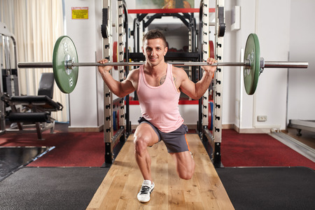 lunges: Man doing barbell lunges to train legs in the gym Stock Photo