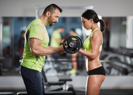 Personal trainer helping a woman with barbell biceps curl workout