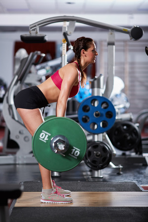 lats: Young woman doing deadlift with heavy barbell in the gym Stock Photo