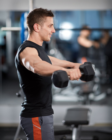 deltoid: Man doing shoulder workout with dumbbells in the gym Stock Photo