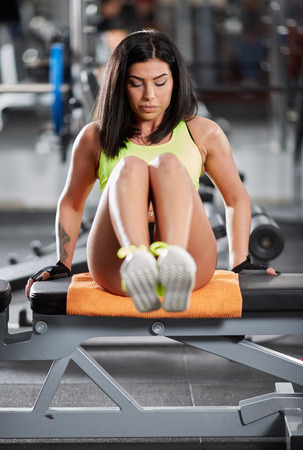 crunches: Athletic young woman at the gym doing abs crunches on a bench
