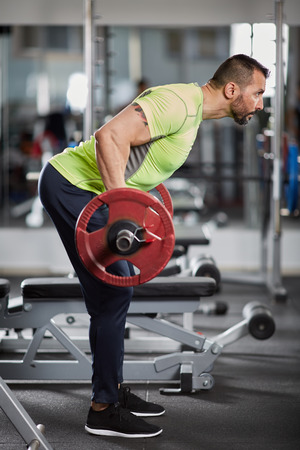 dorsal: Athletic man doing barbell row in the gym for back workout