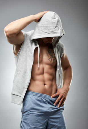unbuttoned: Fitness male model posing in a hooded unbuttoned shirt over gray background Stock Photo