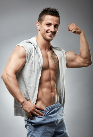 Fitness male model posing in a hooded unbuttoned shirt over gray background Stock Photo